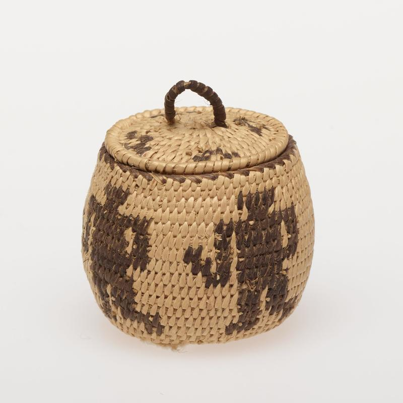 Miniature round basket with cover; coiled. Design consists of four human figures. Cover has coyote tracks. Colors are natural and black.