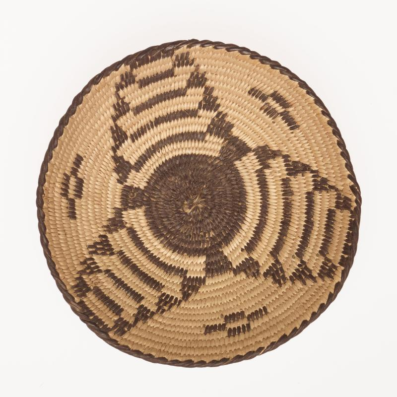 small, shallow, saucer-shaped basket; finely coiled; design is a stepped, three-pointed star; the center is a black disc (devil's claw), and the points of the star are composed of alternate rows of natural and black