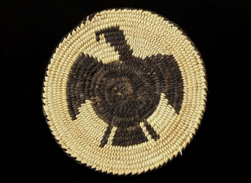 small round coiled plaque; design is that of an eagle; colors are natural and black