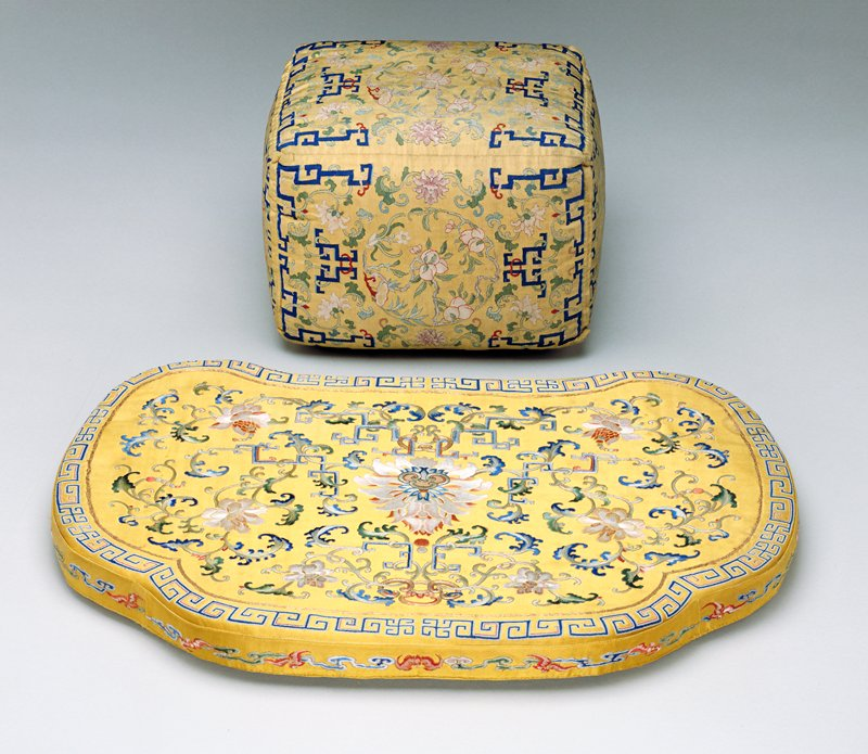 Chair cushion of yellow satin embroidered in satin stitch. The central panel has a design of peonies, trailing vines and square spirals in shades of pink, blue, green and yellow. The shaped border is decorated with running meander and swastika in blue and red in knot stitch. Central peony of panel also carries knot stitch in a fungus motif. Border edged with inner line of couched gold threads.