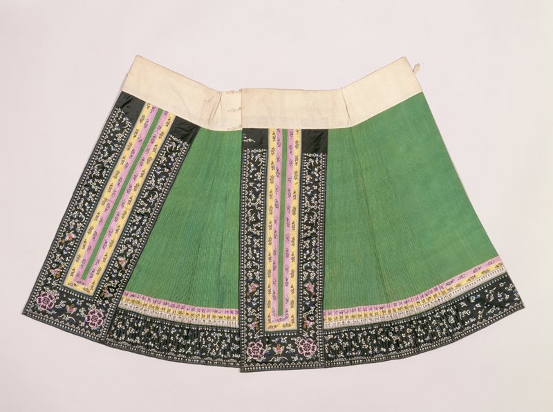 Skirt of emerald green silk of bamboo pattern with stitched, accordion pleated side sections. Main panels and bottom trimmed with elaborate border of bands of embroidered black, yellow, lavendar and white satin with butterflies, bats and floral sparys in colors. In bottom corners of panels, applique medallions with design of cut-out bars and good luck character in black on lavendar ground. Panels lined with magenta silk.