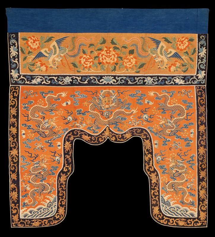 Shaped altar frontal of pale brick red and gold k'ossu. Design of lower section carries five five-clawed dragons in gold with precious symbols, loose clouds, bats and the eternal sea in shades of blue and pale yellow. In the upper, valance section of gold k'ossu, set off from lower section by a band of dark blue k'ossu with running lotus design in shades of lighter blue, appear large peonies and phoenix in shades of pink, yellow, green, blue, and pale rust color. Painted details in valance section. The lower section is bordered with a band of black k'ossu with the running lotus design in gold. Lining and hanging band of blue cotton. Inscription on back.