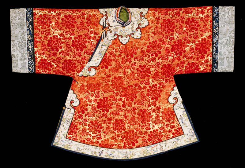 Robe or jacket of cut red velvet on a gold woven background. The design consists of large peony blossoms and butterflies. Shaped collar band and skirt borders of white satin embroidered in a landscape design with figures of women; couched and satin stitch in pastel colors. Wide sleeves with cuffs of pale blue cut velvet of Hundred Antiques design. Cuffs bordered at upper edge with a band of black satin embroidered with flowers and emblems in shades of blue. Leaf-green satin lining. A woman's robe.