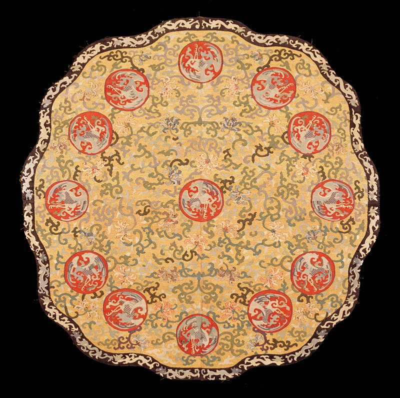 Table cover, shaped, circular, of k'ossu with gold ground. In a field of lotus blossoms with trailing leaves are spaced medallions containing phoenix on a red ground one medallion in center; the other twelve encircling it. Colors include shades of blue, green, pink, violet, red and pale orange. Border of black k'ossu with cursive profile dragons in blue, pink and pale green. Cf. drawing of dragons with that on 42.8.125 (Lama temple, theatrical robes) Lining of yellow satin damask with medallion design.