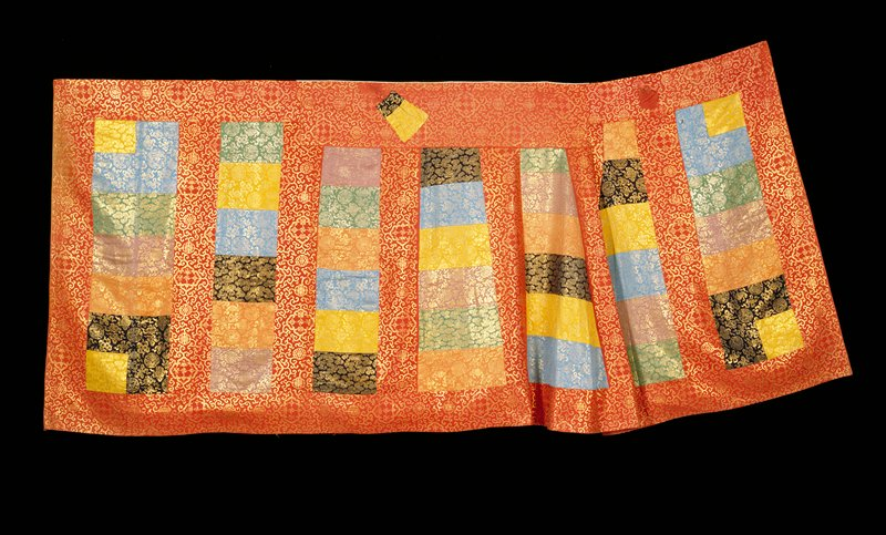 Buddhist priest robe of many squares of brocade ingold and colors green, mulberry, blue, orange, yellow, red, deep blue, and mauve. The outer border and intervening wide bands are of the red brocade which thus predominates. One end of the robe is gored. Lining of red silk.