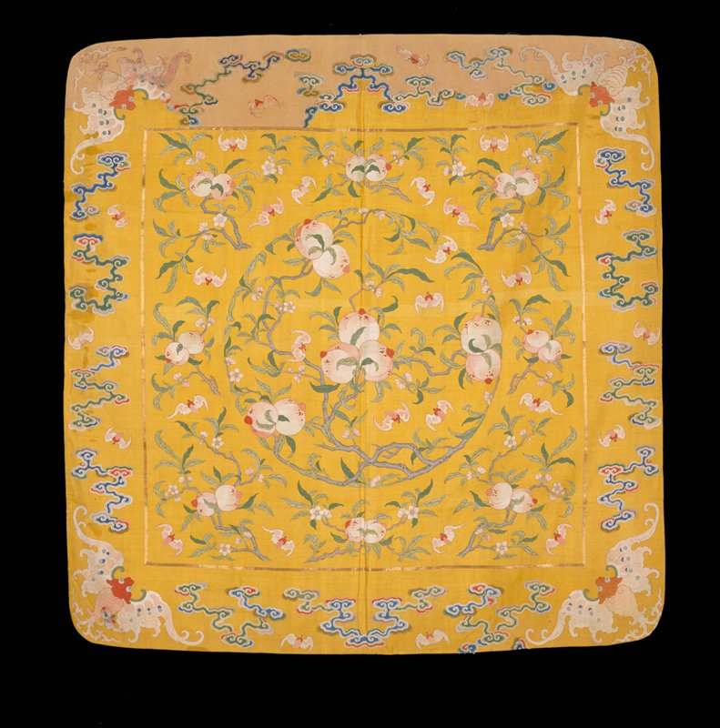 Square hanging of yellow k'ossu with design of peaches, branches and bats. A large central medallion within a panel set off from the border by a narrow band of couched gold threads. In each corner of the border a large bat, with smaller bats and loose clouds in intervening spaces. Chiefly pink, green, and yellow. Lining of pale yellow silk with medallion design. Inscription.