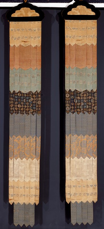 Temple banners, pair, made up of five long strips of various brocades and attached to a flat, shaped plaque of wood covered with gold-colored satin brocade and bordered with a shaped band of brown velvet. The brocades making up each banner strip include pale gold-colored satin with rows of dragon medallions and stylizedclouds in gold and colors; tan and gold; green satin with dragon medaliions and clouds; blue with large medallion diaper; deep gold color with large flowers in green; etc. Lining of faded brick-red raw silk.