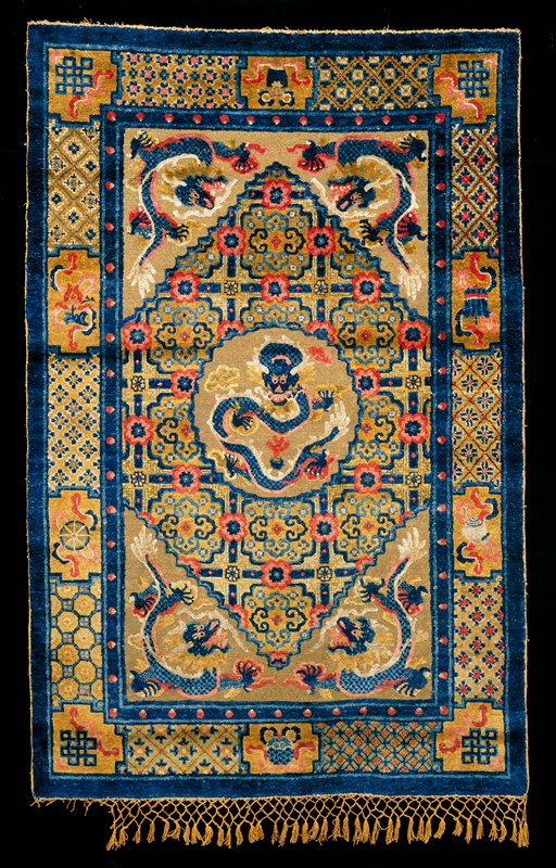Silk rug, the central panel containing a shaped floral medallion on a solid gold ground. In the medallion a five-clawed dragon in blue and red; in each corner of the panel, a five-clawed dragon in blue and red. Three borders the inner one with spaced red disks on a blue ground; The central one with a diapered floral ground and small shaped panels containing the Buddhist symbols. The outer one plain blue. Prevailing tones blue and dull yellow. Sides overcast, ends finished with silk fringe. Cotton warp, sehna knot.