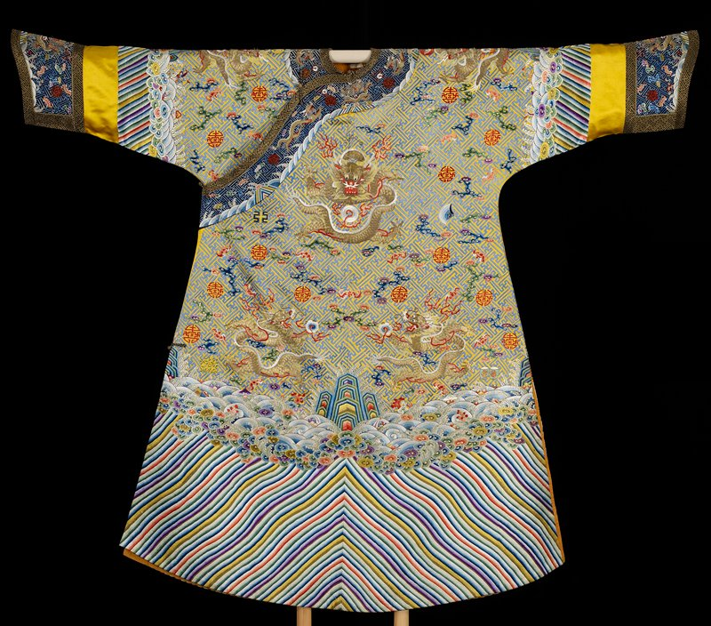 Imperial 12-symbol robe of embroidered yellow satin with swastika fret diaper ground in blue. Nine 5-clawed dragons in gold, those in profile clutching the Heavenly Jewel. In background in addition to 12 ancient symbols, loose cloud forms, bats, and long life characters in shades of blue, green, red, pink, lavendar, and strong violet. Cf. 42.8.44 for same strong purple. Conventional border of slightly wavy slanting stripes in body colors, tight clouds, rolling waves, and lively spray inw hch appear swastikas and branches of coral. Note mass effect of coral here. Below border on sleeve a narrow strip of gold-colored satin. Deep, wide cuffs of black satin embroidered with body designs. Edging and inset of black and gold swastika fret brocade. Collar band same design. Embroidery done chiefly in satin stitch. Couched, laid and stem stitch also used. Robe slit at sides and lined with thin orange silk.