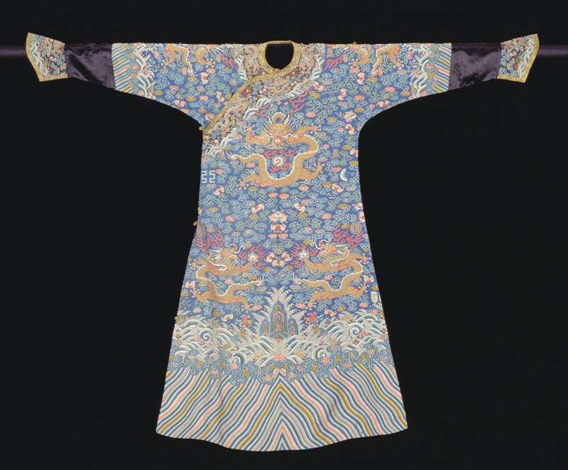 Imperial Twelve Symbol robe of blue k'ossu with nine 5-clawed dragons in gold, those in profile clutching the Heavenly Jewel. In the ground, in addition to twelve ancient symbols, loose clouds, swastikas, bats, and long-life characters in shades of blue, green, red, pink, yellow, soft violet, olive-green, and gold thread. Conventional border of slightly wavy slanting stripes; tight clouds, and rolling waves among which appear emblems of Eight Precious Things and branches of Coral. Below border on sleeves a strip of black satin. Cuffs and collar band of dark blue k'ossu with dragons, clouds, bats, etc. Edging of gold and black brocade. Painted details. Robe slit at sides and lined with thin, diapered blue silk. This robe has been reduced in size by cutting the side seams down. Cf. dimensions of 42.8.10