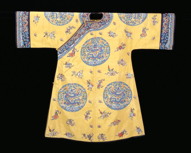 Imperial robe of yellow k'ossu with eight large medallions, each containing a 5-clawed dragon in blue grasping the Heavenly Jewel. Beneath the dragon waves and the sacred mountain, and surrounding trim tight clouds, bats, and swastikas. In the spaces between the medallions embroidered Buddhist and Taoist symbols, bats, and swastikas. Colors in medallions are shades of blue, red, olive green, soft violet, and coral. Colors of the embroidered motifs, worked in satin, laid and outline stitch, are shades of green, red, pink, blue, and brown, mauve and grey. Wide sleeves with band of dark blue k'ossu with Universe design edged with a strip of plain gold k'ossu. Collar of same. Coat slit at sides, and bound around front, bottom, and openings with black satin. Lining of yellow satin damask of medallion design. Inscription in front and at back of neck. Perhaps a woman's coat. K'ossu very firm.