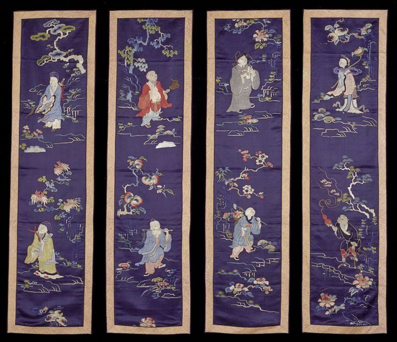 One of a set of four wall hangings of embroidered deep blue satin. Each has a design of two of the Eight Immortals. Floral sprays and boughs in the ground. Satin and knot stitch in shades of green, blue, peach, pink, red, yellow, and tan. Border of gold and salmon-colored brocade with design of symbols and dragon medallions. Former Classification: Textiles - Tapestry