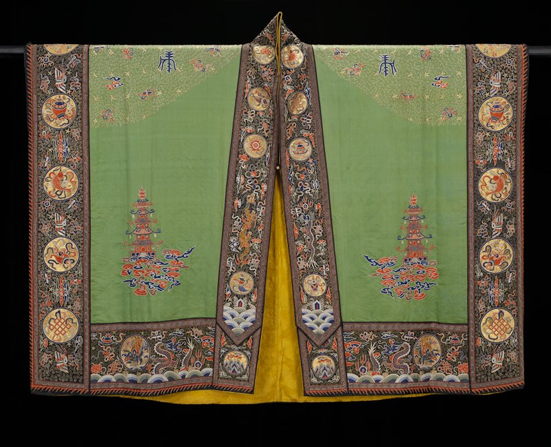 Taoist priest robe of embroidered grass-green satin. On back and shoulders an all-over tendril ground of cuched gold threads. On back conventional Taoist motive, large triple dragon medallions, bats, clouds, and Buddhist emblems in couched gold threads and couched twist in colors. On the front, two sacred pagodas. Borders of black satin with couched gold medallions containing Buddhist symbols in colors, dragons, clouds, Heavenly Jewel, and other symbols in couched twist stitch. Lining of gold-colored damask of cloud pattern.