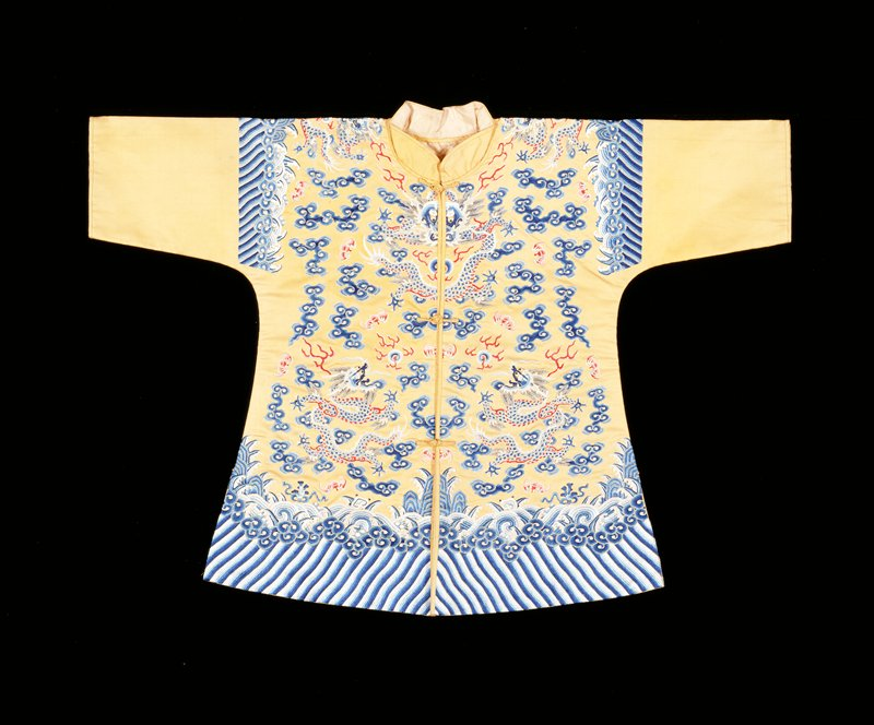 Child's coat of imperial yellow silk embroidered in shades of blue, red, and pink. Eight 5-clawed dragons, bats, and sprawling, tight-headed clouds. Conventional border of slightly wavy short lines; tight clouds; rolling waves in which appear branches of coral. Border entirely in blue and white. Sleeves below border area are plain. Plain upstanding collar, fastening in front. Lining of long-life medallion damask.