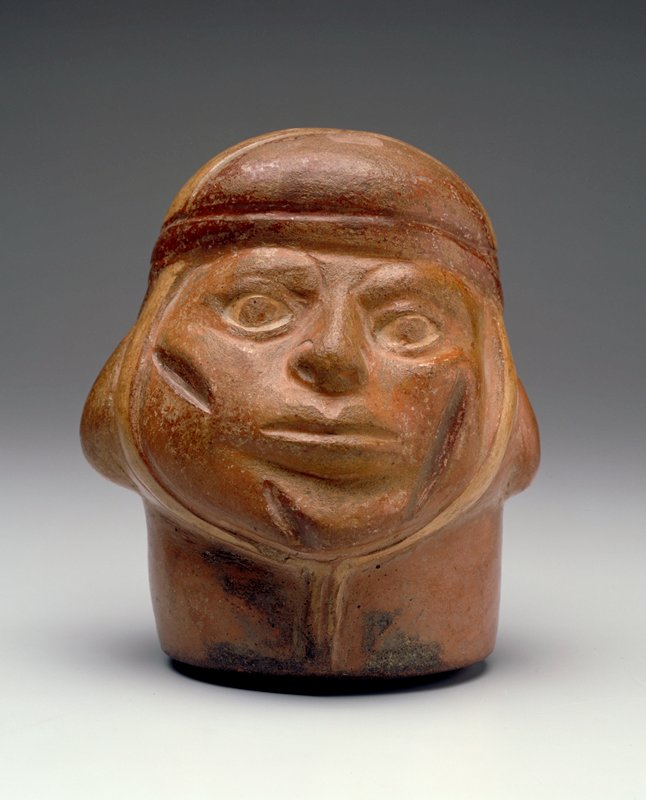 Portrait vase representing the head of warrior with three scars on his face. The head is closely wrapped in a scarf that ties under the chin and is bound by a band around the forehead. The expression of the face reflects clearly the suffering of the wounded man.