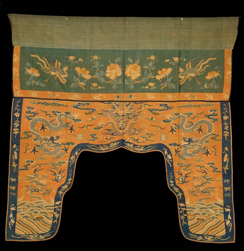 Valance shaped, of faded rust-red, K'ossu bordered by a dark blue band carrying sprays of various flowers. In the field, five five-clawed dragons, three in gold and two in pale blue, pursue the heavenly jewel among lossely drawn clouds and bats. At the base of the side panels, slanting wavy stripes scattered with jui-type clouds and rolling billows. Spray, jewels and artemesia leaf emerge from waves. Across the top of the valance a broad band of bluish-green K;ossu carrying large sparys of peonies flanked by phoenix in flight. Dominant colors are rust, blue, brown, cream and deep peach. K'ossu closely woven. Lining of tan cotton.