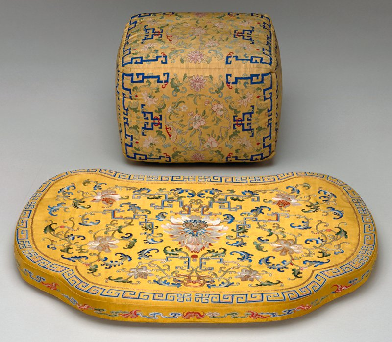 Elbow cushion, covered in fine yellow k'ossu with side panels carrying a design of medallions made up of peaches in groups of three, branches and blossoms. In the surrounding area, trailing branches of peony and fretwork end borders in dark blue. End panels centered with large peony blossoms and leaves. Buttoned slipcover of chatruese green brocade with a swastika fret diaper and an all-over design of flowers and leaves in shades of pink, mauve, and blue.