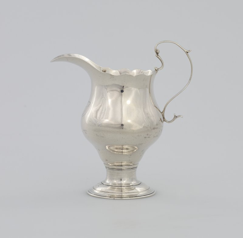 creamer, with scroll cut lip and S-scroll handle, on circular molded foot, monogram on front: [MD]