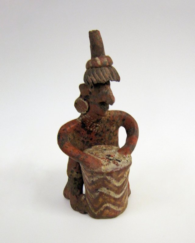 Figure of a drummer. Standing figure with fantastic beak-nosed face, mop-like headdress, and disk earrings. The arms are bent at the elbow and rest on a high cylindrical drum decorated with zigzag stripes in yellow and white on a dark red ground. Painted detail on upper body.