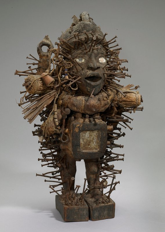 Nkisi Nkonde (nail fetish); a fetish figure in wood; the surface is covered with a variety of accoutrements: nails, reed, shells, bone, wood, string and clay; the 'magic' receptacle in the abdominal area bears a mirror