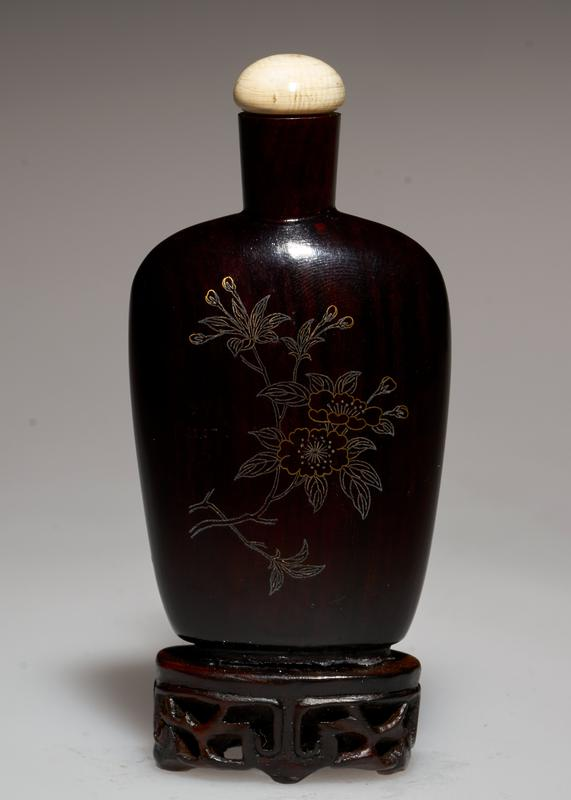Snuff bottle, black wood lacquer, gold floral motif etched, with white jade stopper.