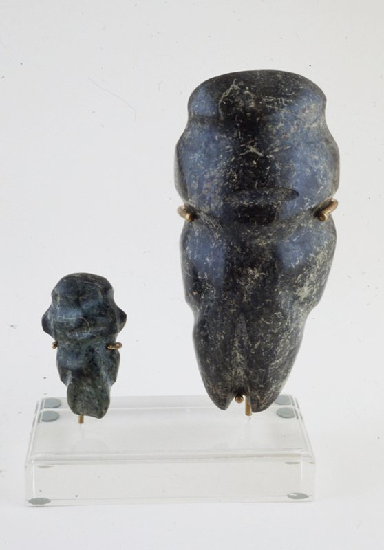 Human figure, stone, Mexican (Mezcala Valley) IV BC-IV AD mounted on plexi base with 77.56.12; cat. card dims H 5-3/4'. Carved by shallow grooves for face, mouth, neck and legs; mottled black-green highly lustrous metadiorite.