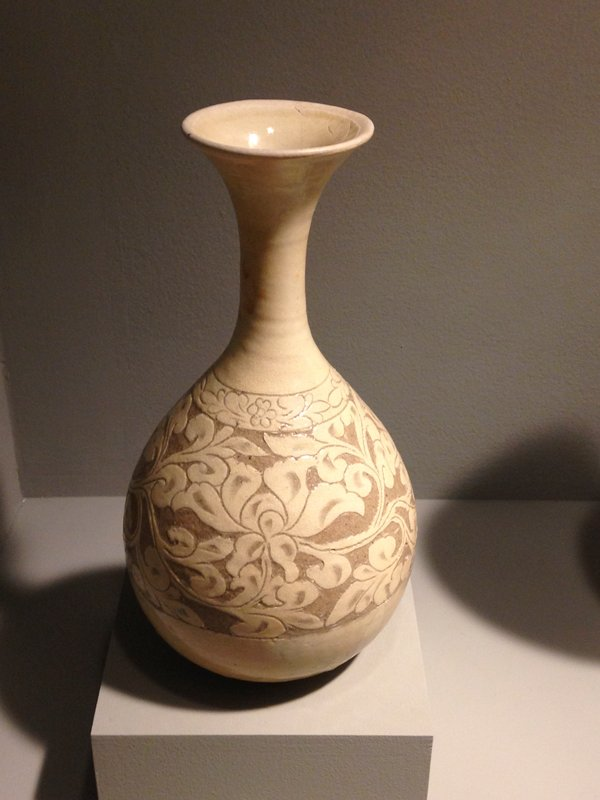 pear-shaped body with long flaring neck; carved floral pattern; knife-cut, slightly flared foot; light tan glaze with light grey stoneware