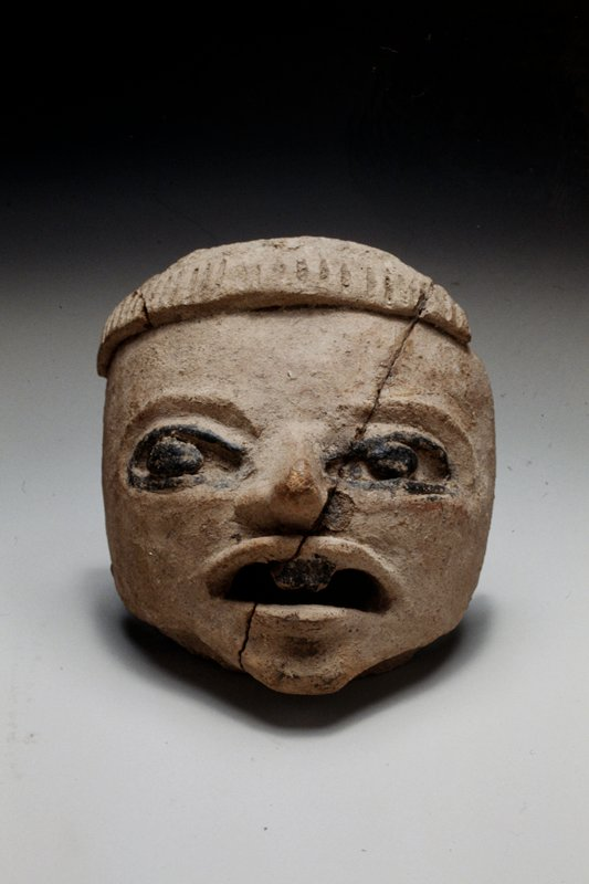 head, hollow fragment, unburnished buff clay with chapopote markings; PIECE IS DAMAGED AND POORLY REPAIRED;