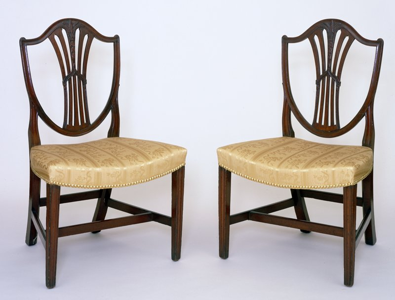 pair of Hepplewhite Side Chairs, c.1795, mahogany. Beaded gothic arches with acorn finials, carved husks and ears of wheat which extend onto the serpentine crest rails, saddle shaped seats and moulded legs connected by stretchers.