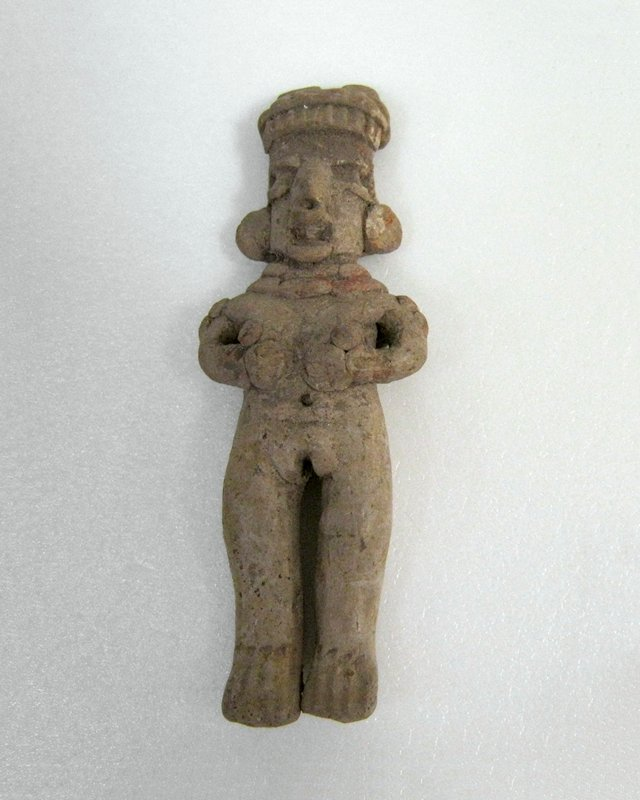 Standing Female Figure holding hands to chest, double necklace, flat earplugs, twin peaked hair with slash hairband. Burnished buff clay, red on necklace, incised fish style feet.