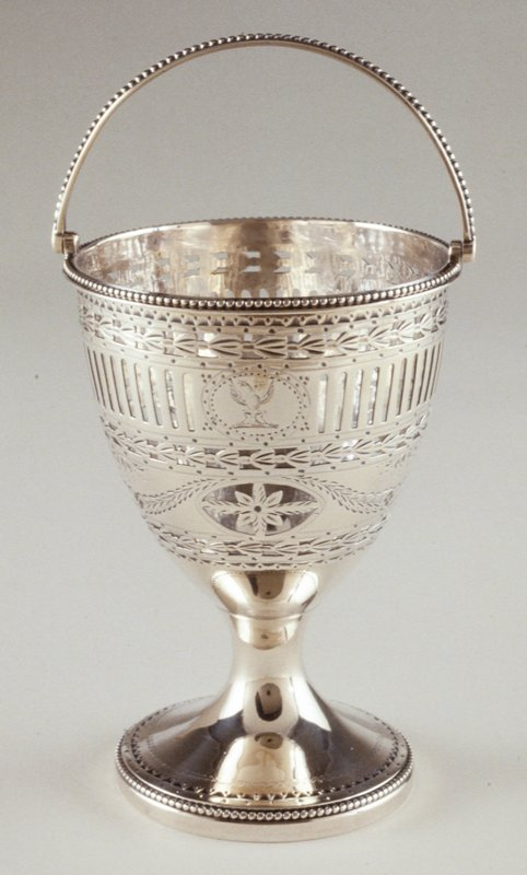 circular basket on circular beaded and bright-cut engraved foot; urn shaped body engraved with floral bands and swags and pierced with rosettes, filleting and tassels; beaded lip and swing handle; engraved underside of foot: L.I.H; fully marked on underside
