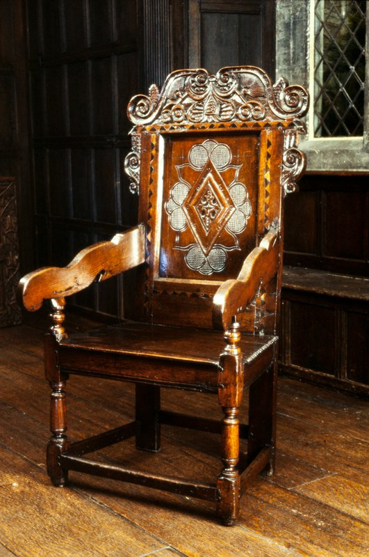 Wainscot; cresting and side pieces carved with scrolls; back panel lozenge design; bands of chevron inlay, turned legs.