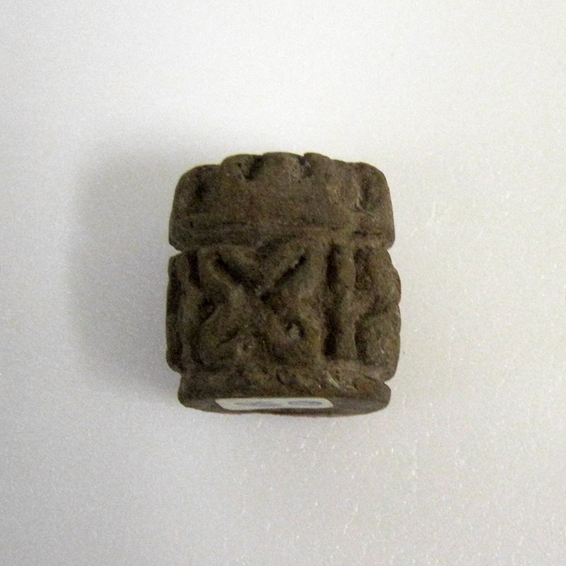 Group of three stamps, one with handle, one elongated and center pierced for rolling, having figures and linear designs, the third for finger rolling, with linear designs ceramic