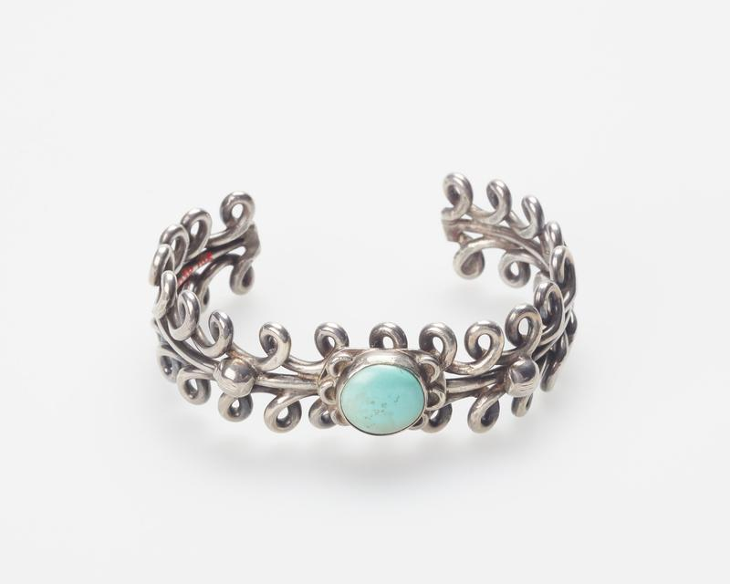 Two looped round silver wires enclosing single round wire, set with single round turquoise at center; teardrop and bent wire decoration. J.#367, Cat.#168.