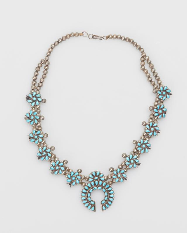 New Zuni; Double strand of small silver beads; (first 10 beads are single); 6 clusters (each side of naja) of 8 'Dewdrop' turquoise each cluster set on pierced extension with 3-pronged squash blossom and button form; naja with twisted wire; 2 rows of sontes, silver drops; 134 stones, string with silver clasp. (serrated bezels, Villa Grove turquoises) J.#428, Cat.#434.