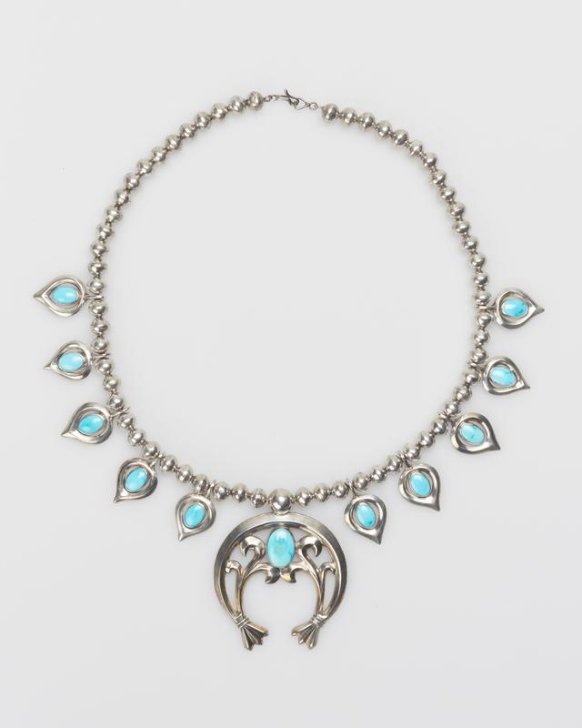 """Single strand of silver beads; 10 cast pear shaped """"pumpkin seeds"""" (silver set with blue elliptical turquoise) cast carinated naja with one elliptical pendant turquoise. J.#496, Cat.#480."""