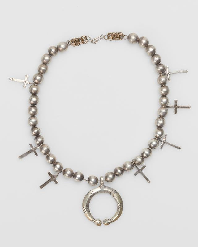 Single strand of fat silver beads; 3 sheet crosses on 1 side, 4 on other; carinated naja with filed designs. J.#471, Cat.#479.