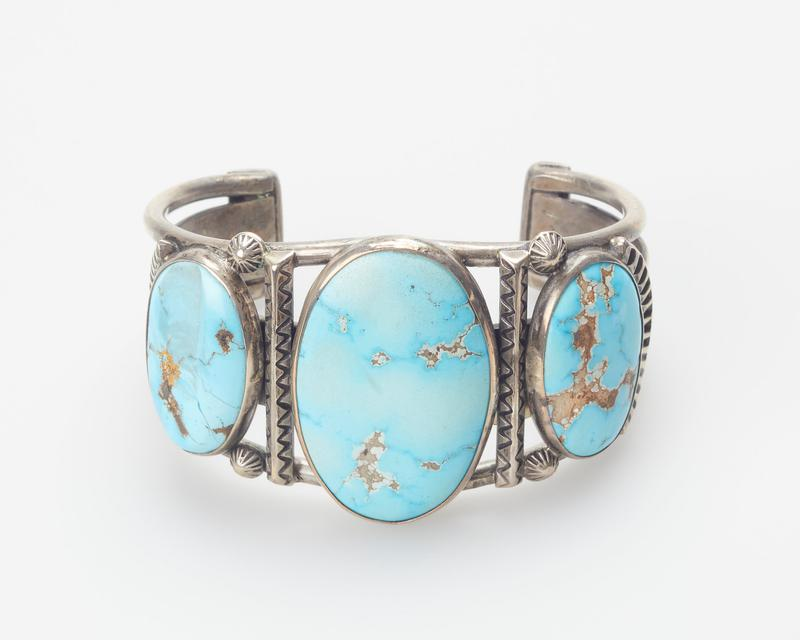 Two round wires enlosing sheet band; set with three large elliptical Cerrillos turquoises; stamped and wire applique decoration, central green turquoise(one turquoise is chipped) cat. 112, J#30