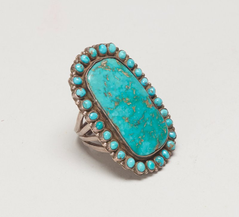 four branched band silver ring with large square Blue Gem turquoise surrounded by 28 small oval turquoises. (central stone somewhat loose) J. #963,Cat# 820, Illus p. 176