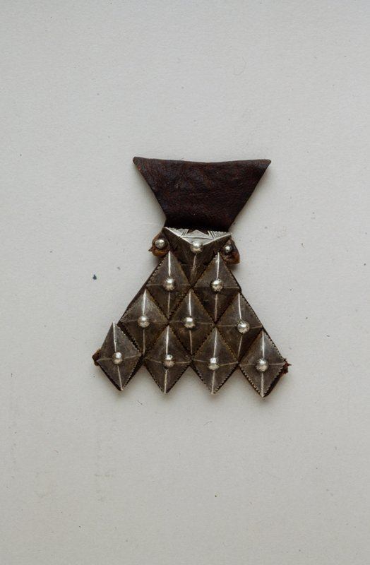 Leather and metal object. Ten metal pieces make up a pyramidal shape, with 9 diamond shaped pieces and one triangular shape; all are topped with a spherical stud. They form a serrated edge along bottom. Top is a leather piece