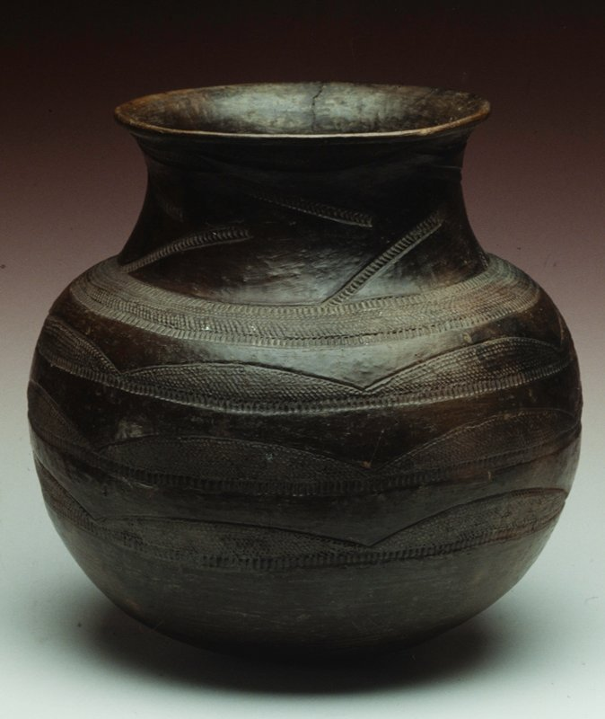 Wide-mouthed vase with incised design pattern with 3 rings of almond shaped designs around body.