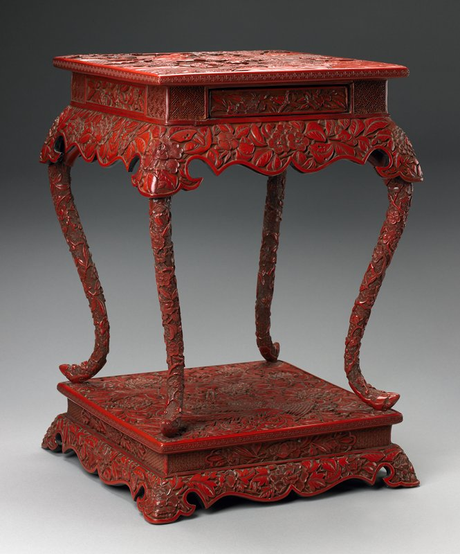 table with drawer, curved legs attached to base, design of landscape on top and paired phoenixes on base; carved cinnabar lacquer