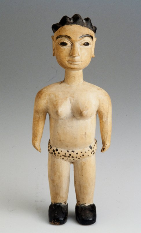 Wooden female figure; with black spotted garment; black shoes, hair, and facial features;