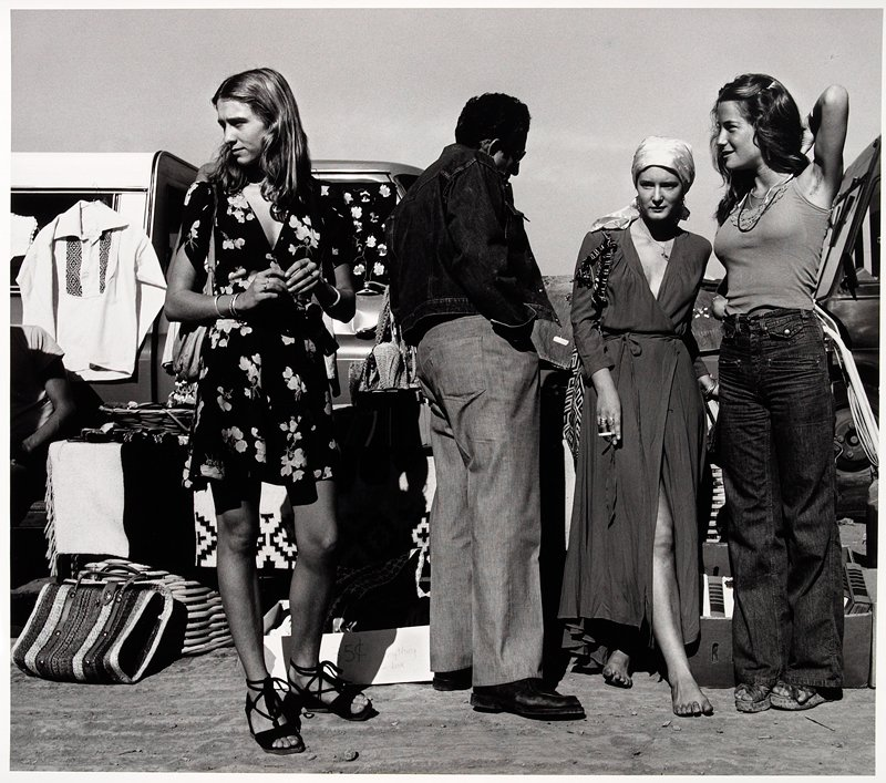 three women and a man standing together looking around