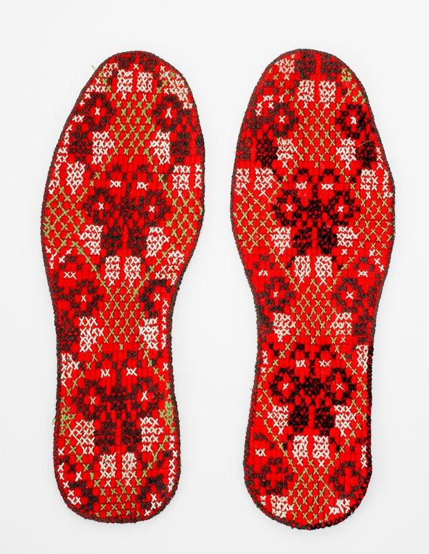 red ground, cross stitched design in black, white green threads