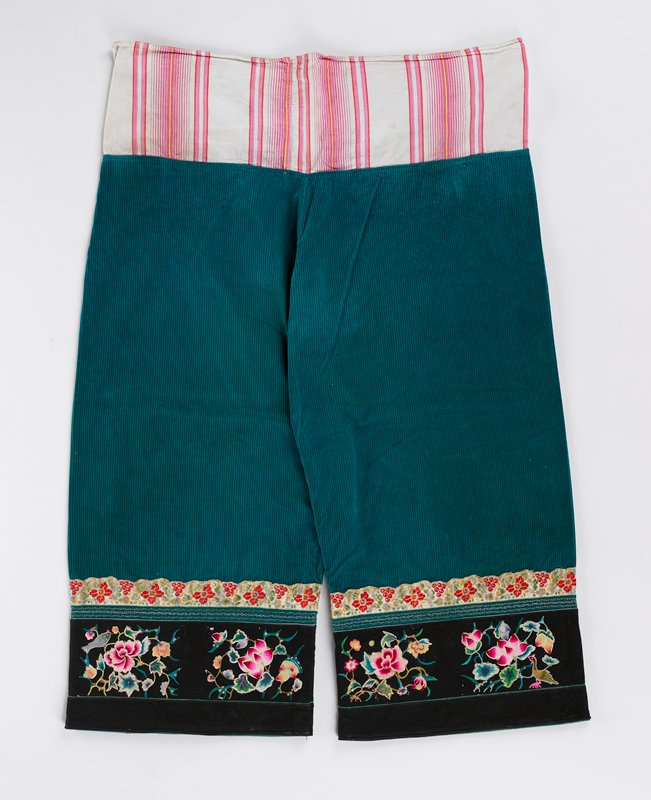 green corduroy, white and pink striped cotton at waist with woven, embroidered bands at bottom of each pant leg
