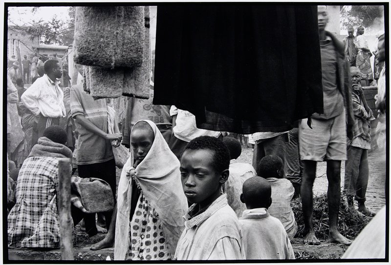 boy and girl in village in front of hanging black cloth