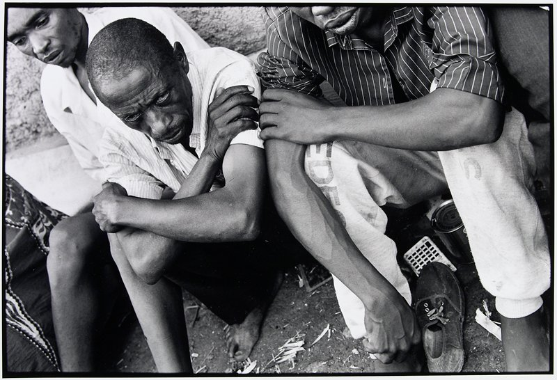 older man sitting on the ground with two others; he is looking at the camera, the man on his right is looking down; the top of the third man's face is not visible