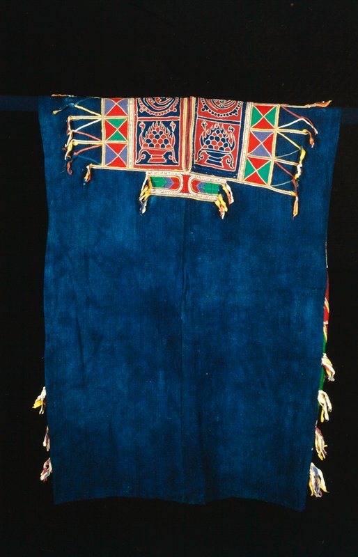 tunic with solid blue body with applique embroidered decorative side panels, shoulders and collar; decorative theme of triangles within squares in colors of red/green or red/blue; ribbons of fabric grouped along edges (extensions of the design)