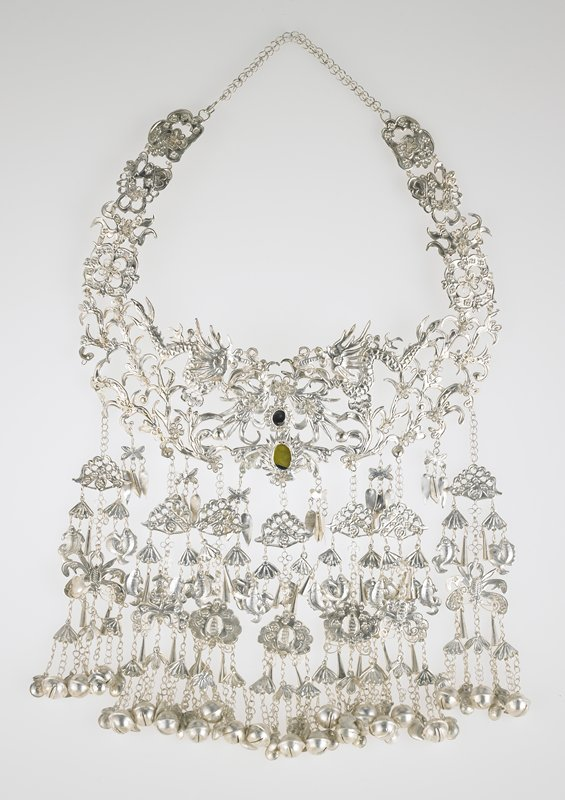 central necklace band has organic design with two central dragons and small oval mirror; hanging from bottom are seven long and six short hanging strands of bells; fish, lotus, horns and other types of designs cut from thin sheets of silver and joined together with small chains of silver